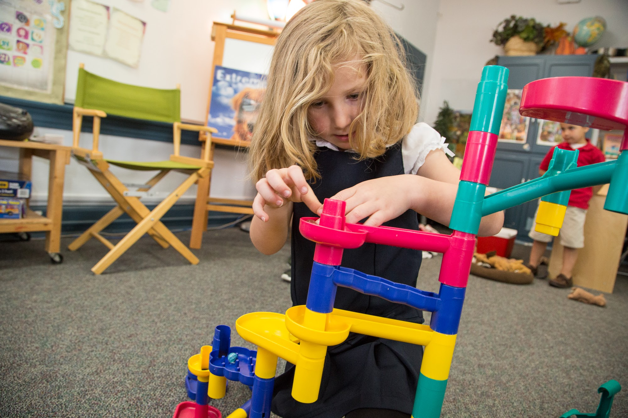 girl creating tower with plastic blocks